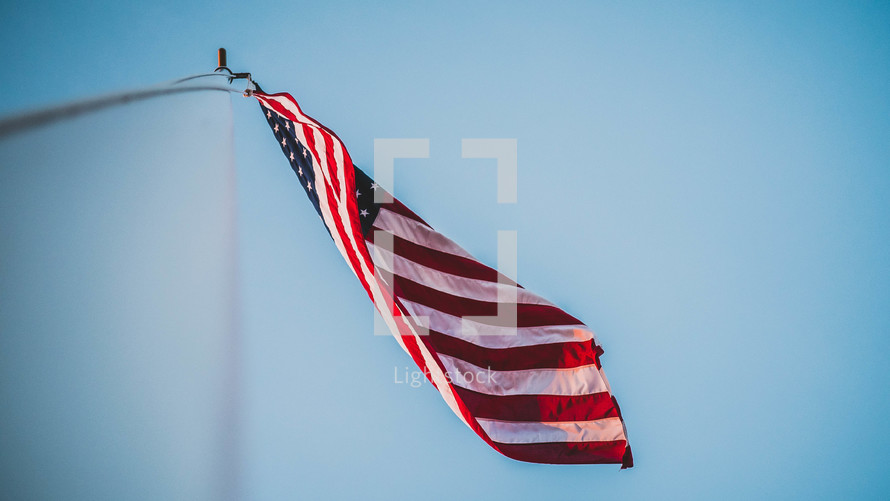 looking up at an American flag on a flagpole