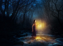 a woman carrying a lantern through a stream in a dark forest