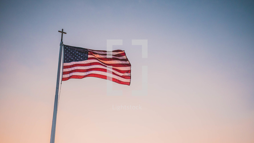 American flag with a cross on the top of the flagpole