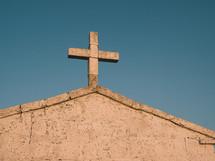 a cross atop a stone chapel in golden dusk light