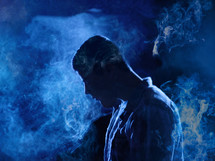 man with head bowed standing in smoke