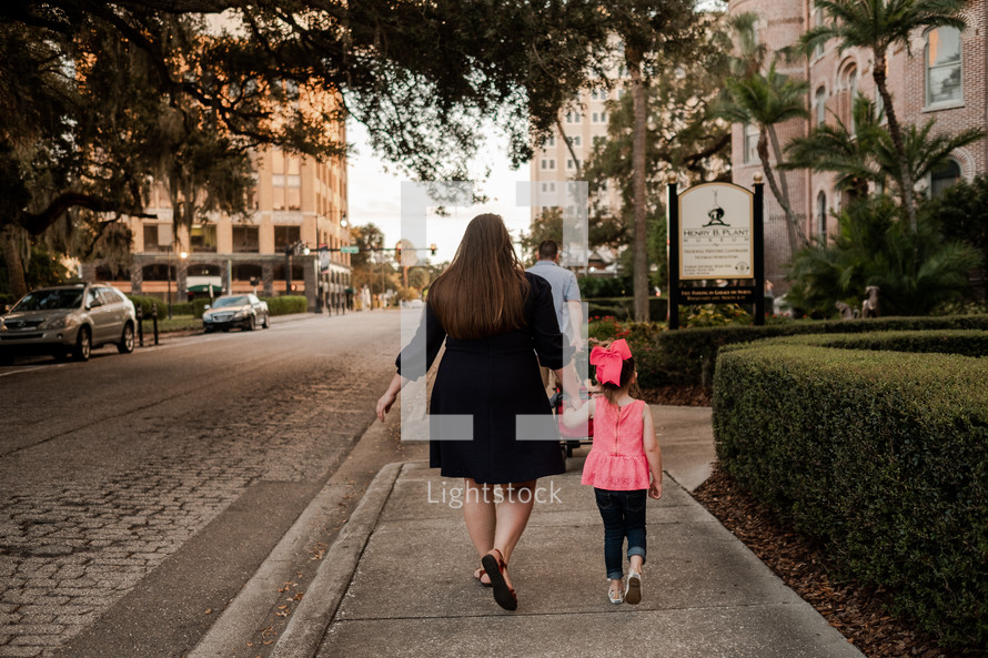 mother and daughter walking on a sidewalk holding hands