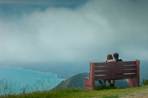 a couple sitting on a bench overlooking a lake in Bir Sur