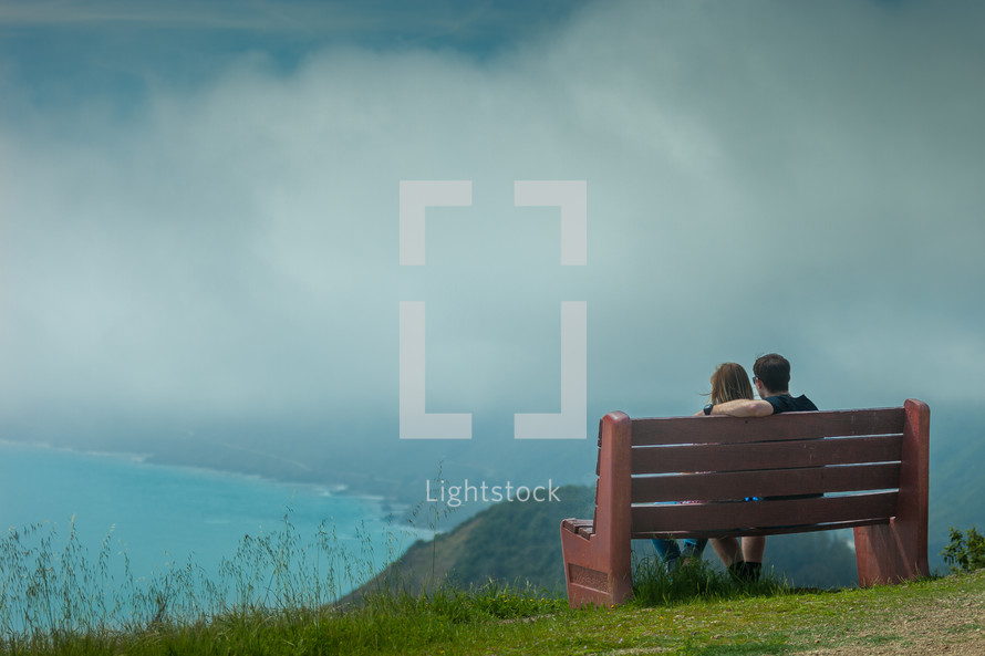 a couple sitting on a bench overlooking the Pacific Ocean in Bir Sur