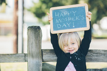 "Girl holding up a ""Happy Mother's Day"" chalk board sign."