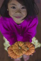 girl holding small pumpkins
