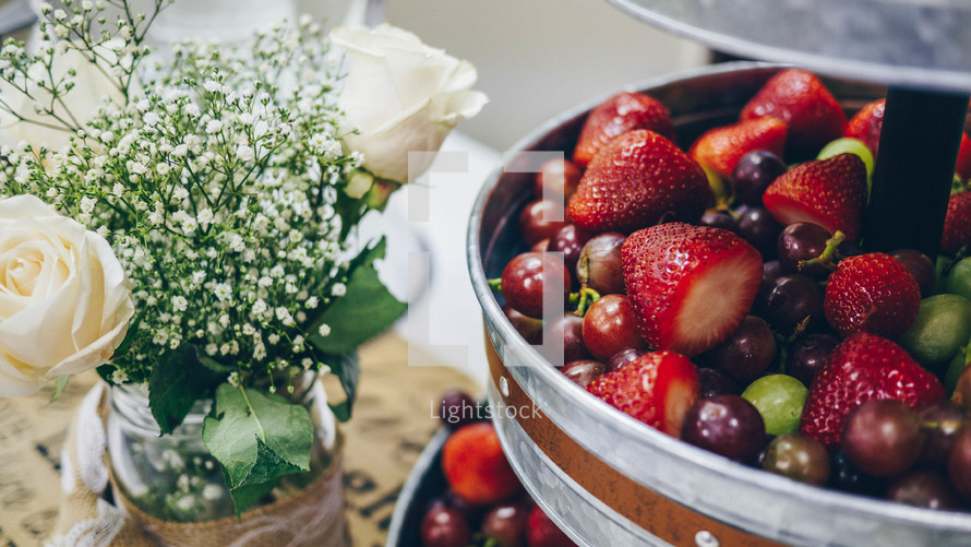 bowl of fruit and flowers in a vase