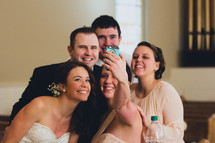 bridesmaids, groomsmen, bride, and groom taking a selfie