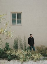 man standing outside by the side of a house