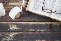 reading glasses on an open Bible and headphones