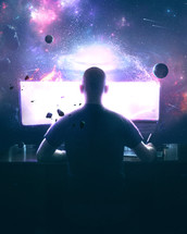 A man designs artwork on a computer with a beautiful space scene