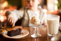 A boy in a restaurant enjoying chocolate cake, milk and ice cream.