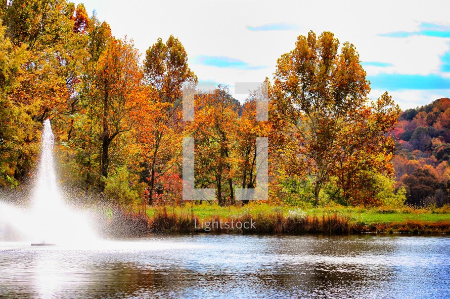 fountain in a lake surrounded by autumn trees