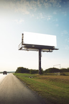 a car passing a blank billboard