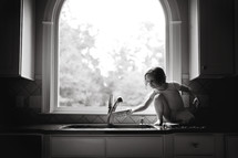 girl child standing on the kitchen counter at the sink