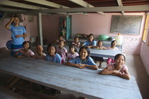 children sitting at desks in a school classrooml
