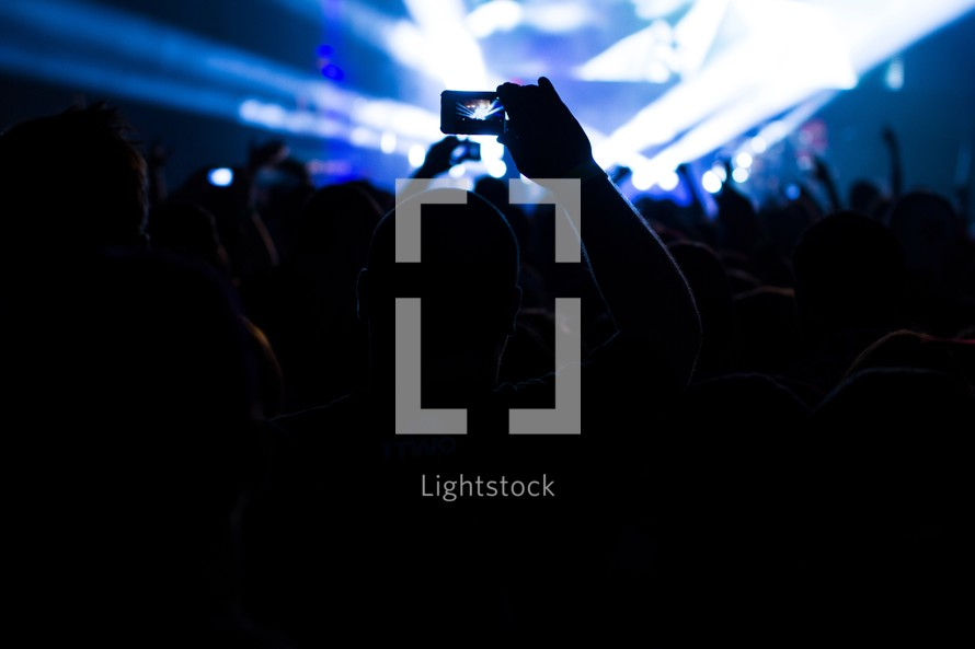 taking a picture with a cell phone at a concert