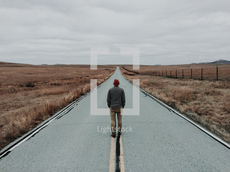 man standing in the middle of a road