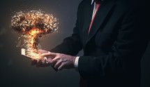 businessman holding an exploding cellphone