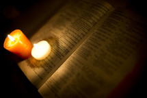red and white candles burning sitting on the pages of an open Bible
