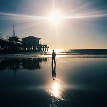 man walking on a beach at sunrise.