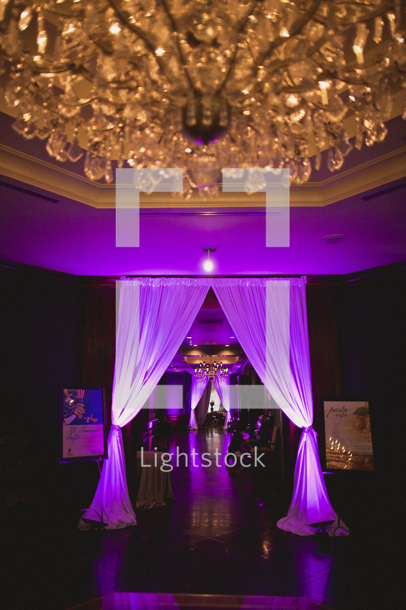 A chandelier hangs from a beautiful reception hall