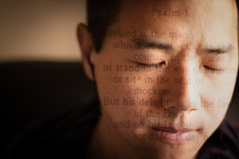 A Bible verse over the face of a man in prayer.