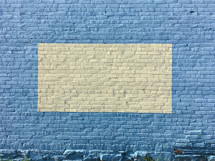 framed pale yellow on blue brick wall background