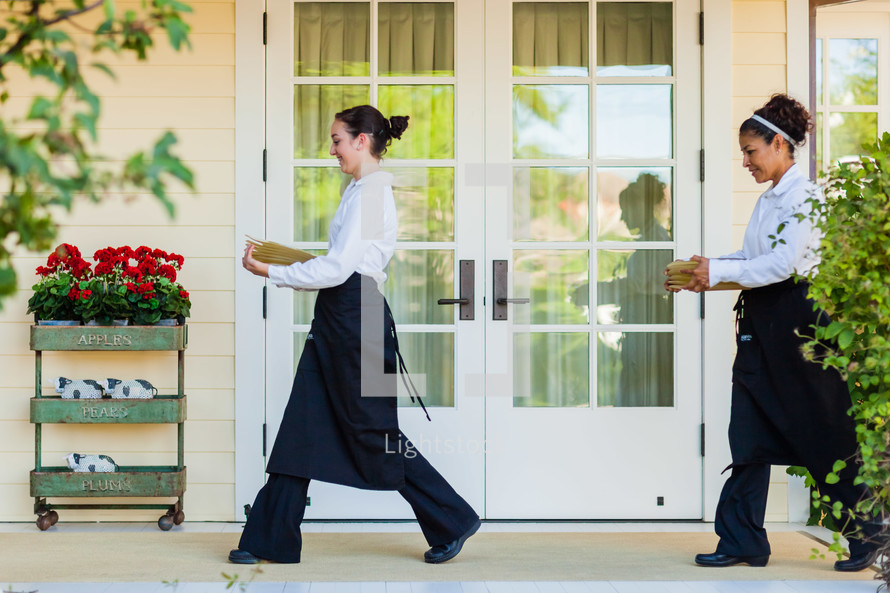 caterers  servers carrying plates across porch.