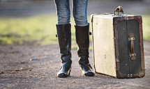 a woman standing on a dirt road next to a suitcase