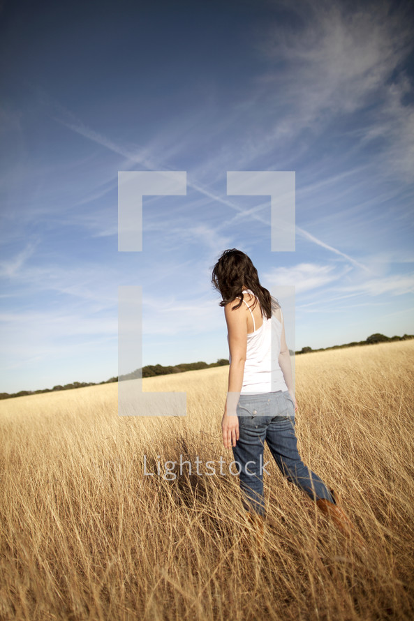 Girl walking through a wheat field