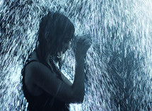 a woman praying under falling rain