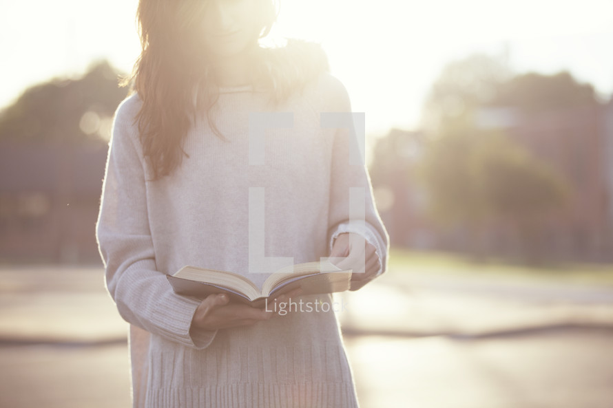Teenage girl reading a Bible with a soft sun flare.