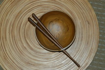 chop sticks resting on a wooden bowl on a bamboo mat