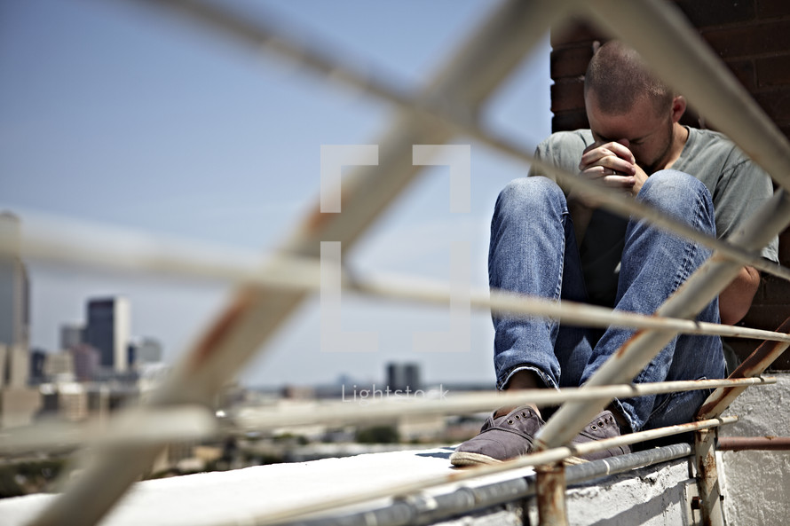 A man praying on a rooftop with hands laced