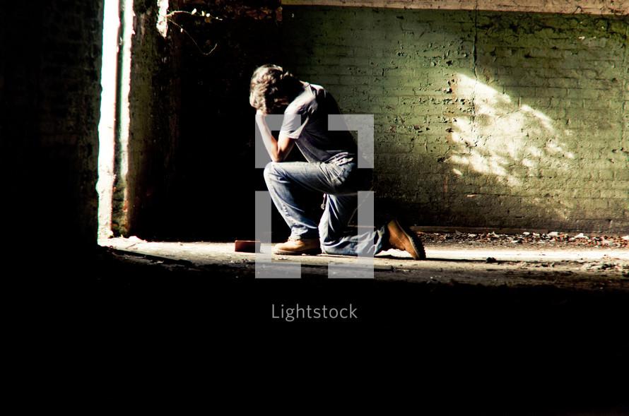Man in jeans kneeling in prayer in front of sunlit doorway of empty brick room and dirty cement floor.