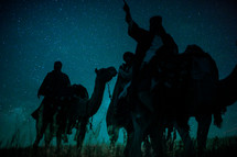 wise men traveling on camels pointing up