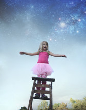 a little girl in a tutu standing on a ladder under the stars