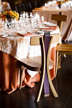 Empty formal dining table party event wood chair made from wine barrel, orange linens flatware, wine glasses