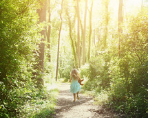 a child with a teddy bear running barefoot on a path through the forest