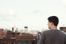 man looking out over the rooftops of a city