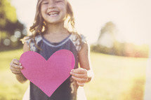 a girl child holding a paper heart