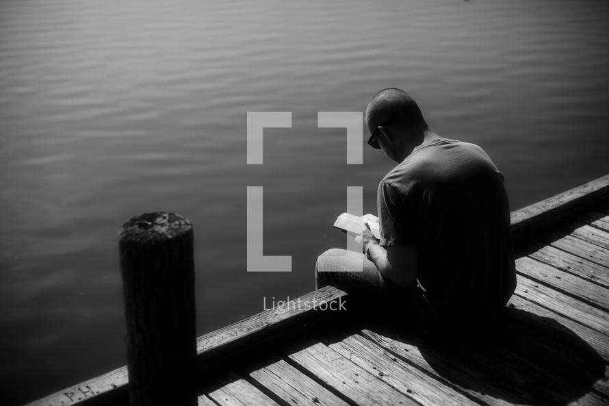 A young man studies the Word on a dock by the still water