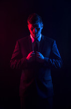 Red and blue light shining on a man who is looking down and holding the lapel of his coat.