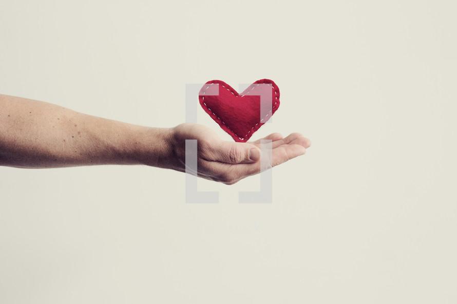 cupped hand holding a felt heart