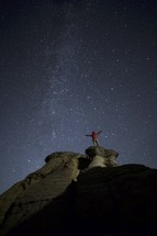 a man with open arms standing on a mountaintop under the stars in a night sky