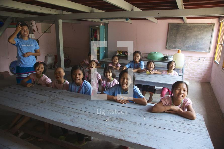 children sitting at desks in a school classrooml