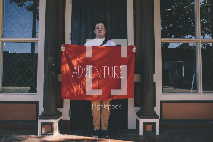 A man holding a red banner with the word adventure on it.