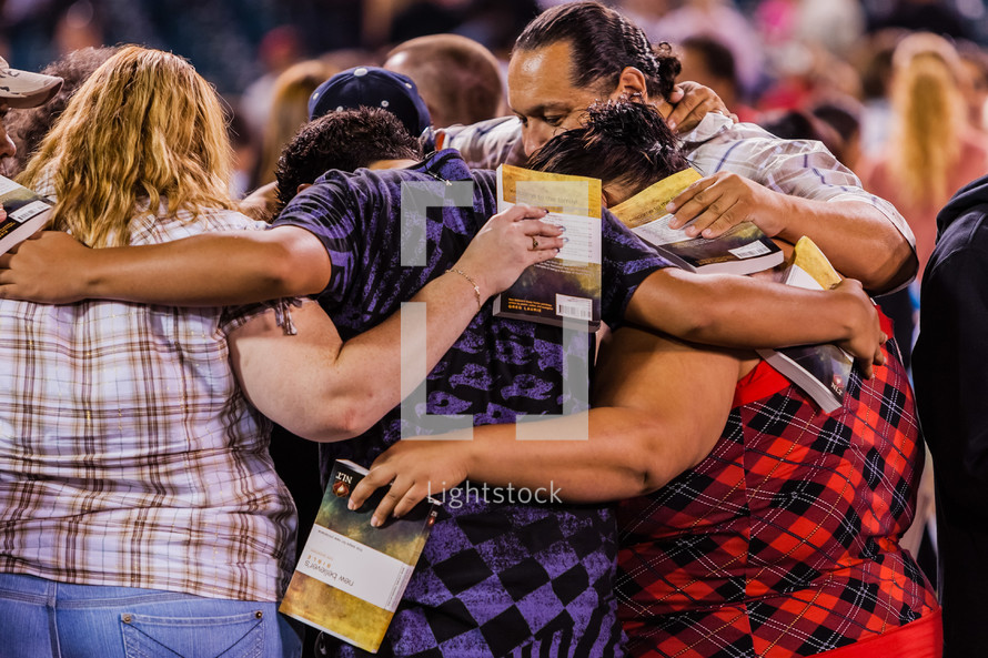 A group of people praying in a circle with arms around each other new believer salvation crusade