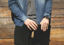torso of a man holding a Bible